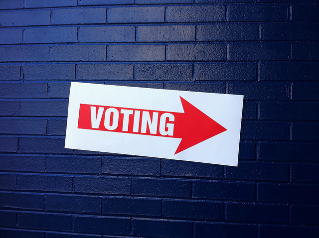 Sign on wall has red arrow with 'VOTING' written on it.