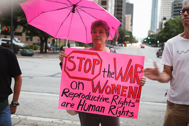 "Woman holds pink sign that reads ""Stop the War on Women: Reproductive Rights are Human Rights"", as she stands under a pink umbrella"